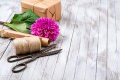 被手工造的礼物盒和桃红色菊花花在木背景 自然样式设计的概念 图库摄影