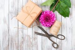 被手工造的礼物盒和桃红色菊花花在木背景 自然样式设计的概念 库存照片