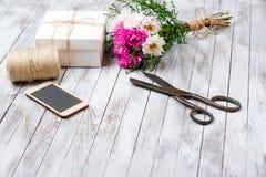 被手工造的礼物盒和桃红色菊花花在木背景 自然样式设计的概念 免版税库存照片