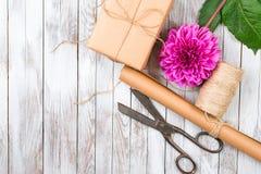 被手工造的礼物盒和桃红色菊花花在木背景 自然样式设计的概念 库存图片