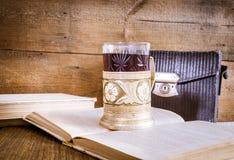 被打开的书、茶在沿海航船和葡萄酒照片请求 免版税图库摄影