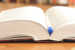 被打开的书在与笔的桌里 图库摄影