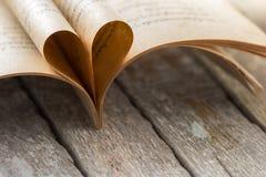 从被打开的书页的心脏形状在木背景 免版税图库摄影