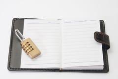 被打开的减速火箭的纸笔记本以挂锁组合安全 图库摄影