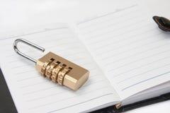 被打开的减速火箭的纸笔记本以挂锁组合安全 免版税图库摄影