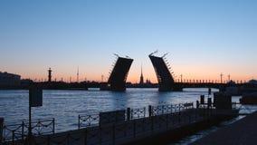 被打开的宫殿桥梁剪影和一个堤防在不眠夜 免版税库存照片