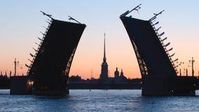 被打开的宫殿桥梁彼得和保罗堡垒早晨-圣彼德堡,俄罗斯剪影和教堂  图库摄影