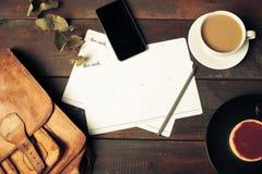 被打开的工艺纸信封、秋叶和咖啡在木桌上 免版税库存图片