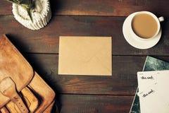 被打开的工艺纸信封、秋叶和咖啡在木桌上 库存图片