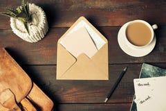 被打开的工艺纸信封、秋叶和咖啡在木桌上 库存照片