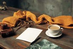 被打开的工艺纸信封、秋叶和咖啡在木桌上 免版税库存照片