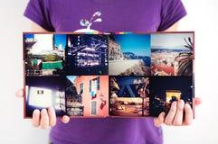 被打开的方形的旅行象册在妇女手上 库存图片