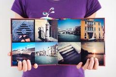 被打开的方形的旅行象册在妇女手上 免版税库存照片
