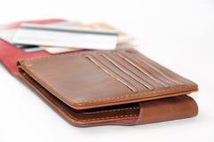 被打开的棕色皮革钱包和信用卡在背景中 免版税图库摄影