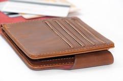 被打开的棕色皮革钱包和信用卡在背景中 免版税库存照片