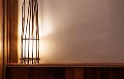 被打开的灯由分支制成在木顶头床和白色墙壁,有拷贝空间的 免版税库存照片