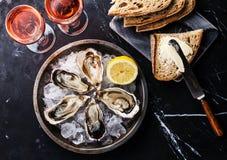 被打开的牡蛎、面包用黄油和玫瑰酒红色 免版税库存图片