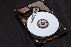 被打开的硬盘从在黑暗的木背景的计算机 艺术射击 库存图片