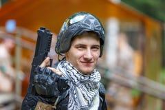 被打开的面具的聪明的男孩与迷彩漆弹运动手枪 免版税库存图片