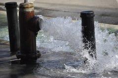 被打开的firehydrant在城市街道 免版税图库摄影