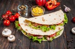 被扭转的三明治在木背景滚动玉米粉薄烙饼两棵片断和菜 免版税库存图片