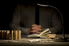 被折叠的手临近书和难题片断 免版税库存图片