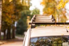 被折叠的梯子说谎在一辆白色汽车顶部 库存照片