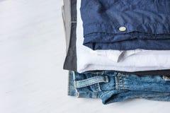 被折叠的牛仔裤棉花裤子和衬衣堆堆在白色木背景架子壁橱 Eco时尚地道经典样式 库存图片