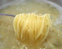 被抱起罐的煮熟的面团面条与叉子的开水 库存图片