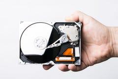 被拆卸的硬盘驱动器在白色背景的男性手上 图库摄影