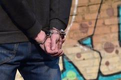 被拘捕的和扣上手铐的违者的背面图反对gr的 免版税库存图片