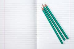 被排行的练习本和三支铅笔 免版税图库摄影
