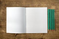 被排行的练习本和四支铅笔 免版税库存图片