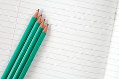 被排行的练习本和四支铅笔 免版税库存照片
