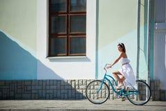 被提炼的妇女骑蓝色葡萄酒自行车在城市街道 免版税库存照片