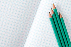 被摆正的练习本和四支铅笔 库存照片