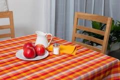 被摆的桌子-叉子和匙子在黄色,红色和橙色布料放置了 库存照片