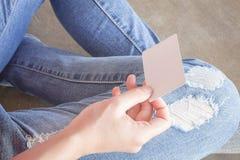 被撕毁的牛仔裤的妇女坐地面 库存图片