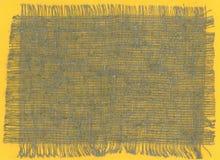 被撕毁的粗糙的粗麻布织品在黄色背景渐近 免版税库存图片