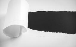 被撕毁的纸在黑背景 库存图片
