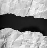 被撕毁的纸在黑背景 免版税库存照片