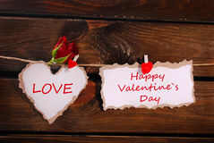 被撕毁的纸垂悬在木墙壁上的心脏和卡片 免版税库存照片