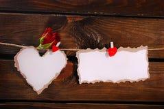 被撕毁的纸垂悬在木墙壁上的心脏和卡片 免版税库存图片