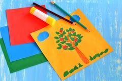 被撕毁的纸夏天拼贴画 云彩,太阳,从被撕毁的纸做的苹果树 婴孩的,孩子,学龄前儿童拼贴画工艺 库存图片