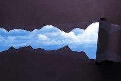 被撕毁的纸有蓝天背景 免版税库存图片