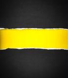被撕毁的黑纸和空间文本的有黄色纸背景 库存图片