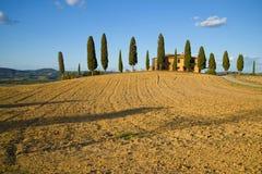 被收获的领域和老别墅在一晴朗的9月天 意大利托斯卡纳 库存照片