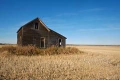 被收获的麦田的被放弃的房子在秋天 免版税库存图片