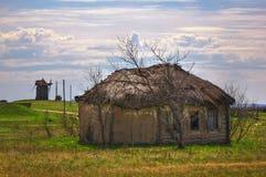 被放弃的俄国村庄 农村房子废墟有茅屋顶的 免版税库存照片