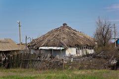 被放弃的俄国村庄 农村房子废墟有茅屋顶的 免版税库存图片